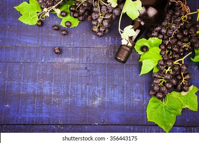 Wine grapes and wine on a wooden background