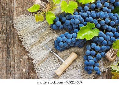 Wine and grapes in vintage setting with corks on wooden table