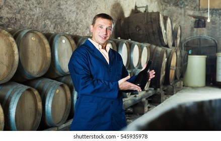 Wine house worker holding bottle near shelves in storage