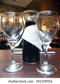 A wine jar with two wine glasses at the restaurant table