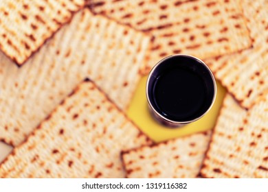 Wine kiddush glass and matzah on the background. Jewish holiday of Passover concept.