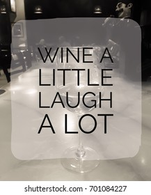 Wine A Little Laugh A Lot Typography Design On Image Of Bar.