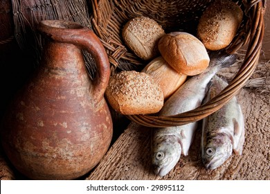 Wine, loaves of bread and fresh fish in an old basket