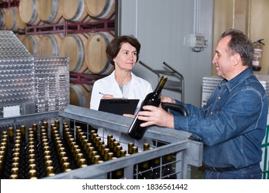 Wine maker showing to expert of the bottles with the wine