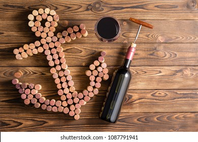 Wine marine theme with unlabelled bottle and corkscrew, glass of red wine and many corks in the shape of an anchor over wooden table viewed from above with copy space