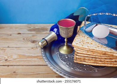 Wine and matzo for Jewish holiday Passover on wooden table