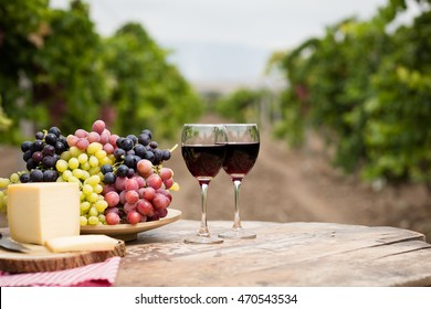 Wine on rustic wood table in vineyard.