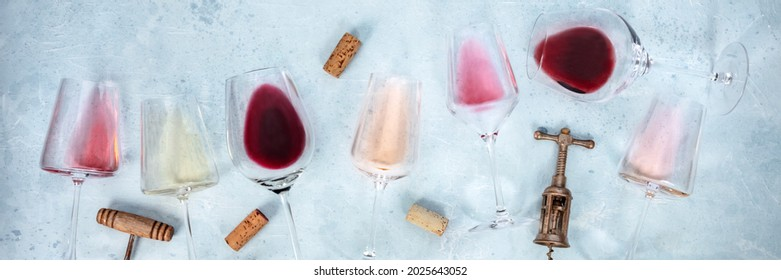 Wine panorama with glasses of rose, red, and white wine, with corscrews and corks, shot from the top. Various colors