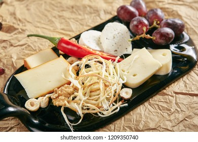 Wine Plate with Cheese Mix, Nuts and Grapes on White Rectangular Flat Plate. Cheeseboard with Pieces of Various Cheese such as Cheddar, Manchego, Gauda and Smoked Cheese