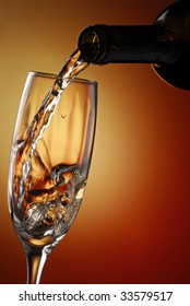 Wine pouring into a glass with abstract background