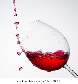 Wine pouring into a glass in square composition and white background