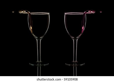 wine pouring out of glasses isolated on black
