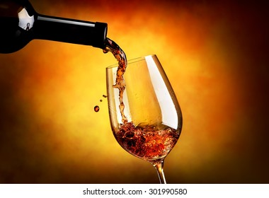 Wine pouring in wineglass on an orange background