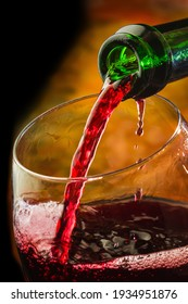 Wine pours into the glass of the bottle on a colored background