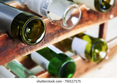 Wine rack in cellar, with wine bottles - on vintage, rustic wooden rack. Focus on front bottle, the rest blurring. For food and drink, dining & alcohol concepts.