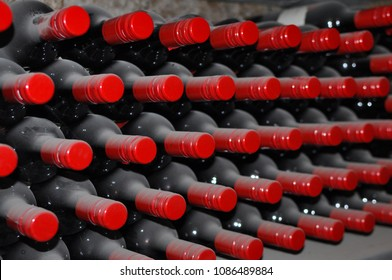 Wine rack storage of vintage dusty wine bottles, in wine cellar of Barossa Valley in South Australia. A soft focus with grain