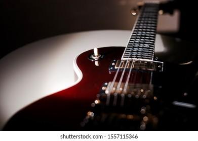 wine red electric guitar closeup . dark background