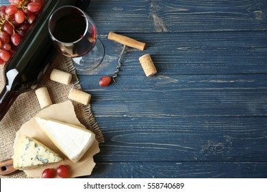Wine, red grape and cheese on wooden background