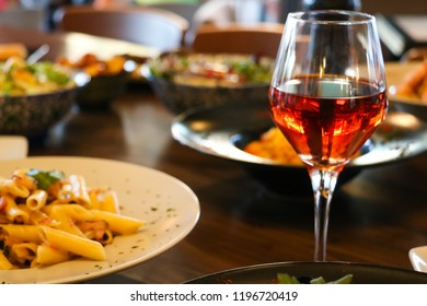 Wine rose in crystal glass with accompanying meal on wooden table. Blur plates with foods background, closeup.
