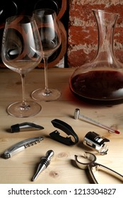 Wine serving kit on a light wood table: 2 glasses with a decanter with red wine and the accessories to open, serve and measure the temperature of the bottle. Background of a typical wine shop.