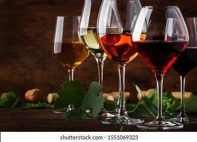 Wine set. Red, white and rose wine in assortment in wineglasses. Wine tasting, vintage wooden background, selective focus, copy space