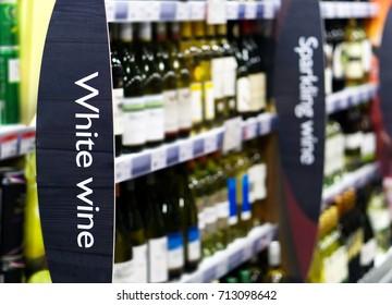 Weinregallaisle im Supermarkt mit Weißwein und im Vordergrund