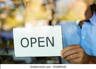Wine shop owner holding open sign