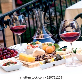 A wine show prepared with a special presentation. Wine carafe and wine glass. Fruits, cheese and appetizer.