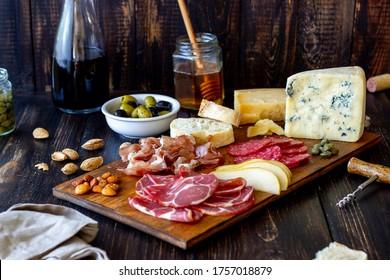 Wine snack. Prosciutto, Parma ham, salami, almonds, olives baguette blue cheese parmesan Antipasti