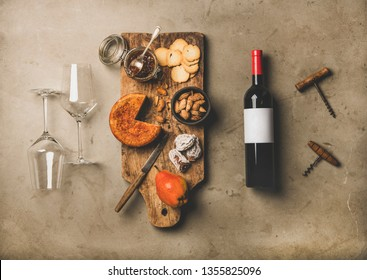 Wine and snack set. Flat-lay of wine bottle with blank label, vintage corkscrews, two wineglasses and cheese and appetizers board over concrete background, top view. Party food concept