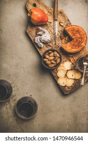 Wine and snack set. Flat-lay of two glasses of red wine, vintage corkscrews, cheese and appetizers on wooden board over dusty concrete background, top view, copy space. Party food concept