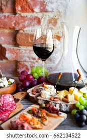 Wine snack set. Glass of red wine, grape, cheese, over rustic wooden background. Top view, copy space, horizontal composition.
