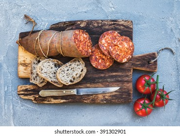 Wine snack set. Hungarian mangalica pork salami sausage, rustic bread and fresh tomatoes on dark wooden board over a rough grey-blue concrete background, top view, horizontal