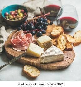 Wine and snack set. Variety of cheese, olives, prosciutto, roasted baguette slices, grapes on wooden board and glasses of red wine over grey marble background, selective focus, square crop