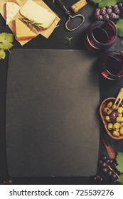 Wine and snack set. Variety of cheese, mediterranean olives, black and green grapes and glasses of red wine over dark background, top view, copy space