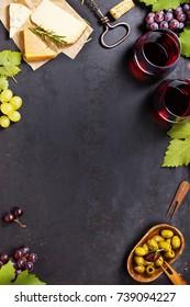 Wein und Snack. Vielfalt von Käse, mediterranen Oliven, schwarz-grüne Weintrauben und Gläser aus Rotwein auf dunklem Hintergrund, Draufsicht, Kopienraum