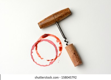 Wine stains cork and corkscrew on paper. Horizontal format. The stains are from wine bottle bottoms and drips.