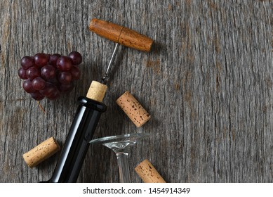 Wine still life with bottle corkscrew, grapes on a rustic wood table. Horizontal with copy space on the right side.