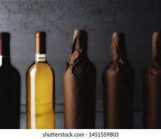 Wine Still Life - Five Wine Bottles, three wrapped in plain paper with one red wine and one white. Strong side light with copy space.