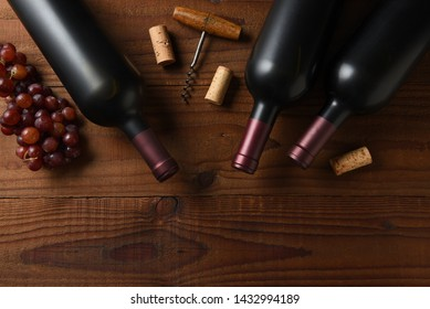 Wine Still Life: Three Cabernet Sauvignon wine bottle short from directly above on a dark wood table with grapes corks and cork screw and copy space.