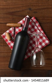 Wine Still Life: Vertical High angle view of a red wine bottle on a red and white checkered napkin with wine glass and corkscrew.
