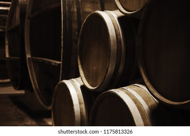 Wine storage. Round wooden barrels in dark winery, close-up photo with selective focus