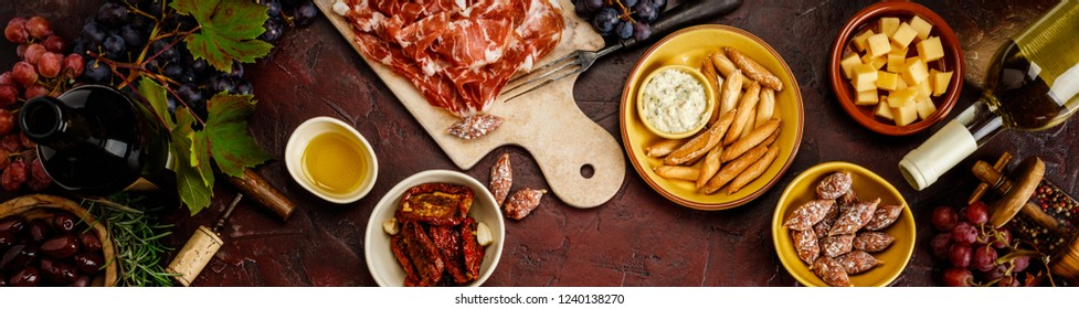 Wine and tapas on red stone background, top view