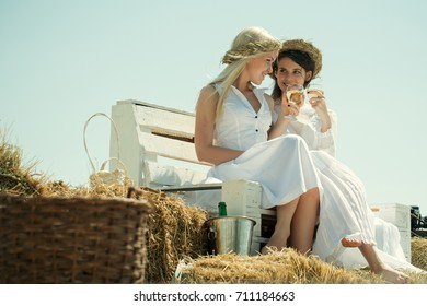 Wine tasting concept. Girlfriends smiling on bench on blue sky. Happy girls with champagne glasses outdoors. Summer vacation, holidays and celebration. Women drinking alcohol on sunny day.