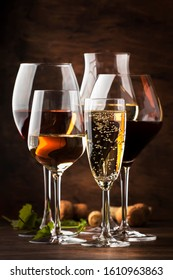Wine tasting concept, still and sparkling wines. Red, white wine, rose and champagne in wine glasses on vintage wooden table background