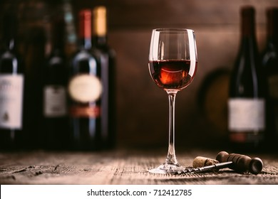 Wine tasting experience in the rustic cellar and wine bar: red wine glass and collection of excellent wines on the background