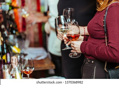 wine tasting: visitors stand near tables with tasting samples and hold glasses of wine.