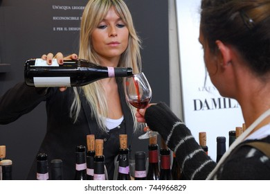 Wine trading fair people taste a wide selection of italian wines blonde woman puring red wine from bottle to glass Turin Italy circa November 2016