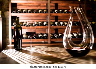 WIne vault place. Wine bottles and wine glass placed on the table and shelves.