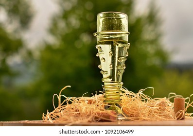wine in a vintage green glass, green blurred background, with cork stumps and wooden straw photo props